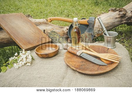 Rustic cooking utensils. Wooden spoon, axe, bowl, knife and cutting board.