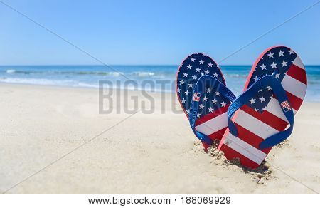 Patriotic USA background with flip flops and decorations on the sandy beach