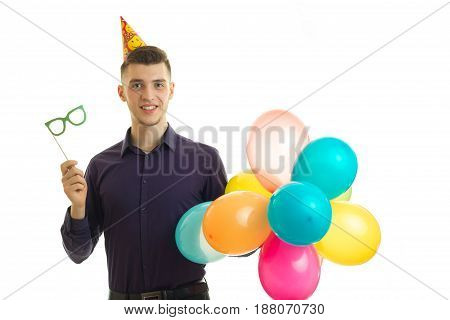 cheerful guy at a birthday party with the paper glasses and balloons in hands isolated on white background