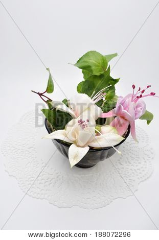 a few really nice flowers of fuchsia and black glass small Cup on a white Lacy napkin