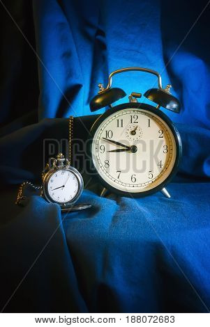 Vintage still life - a retro pocket watch and an alarm clock on a background of dark blue drapery.Time concept soft focus.