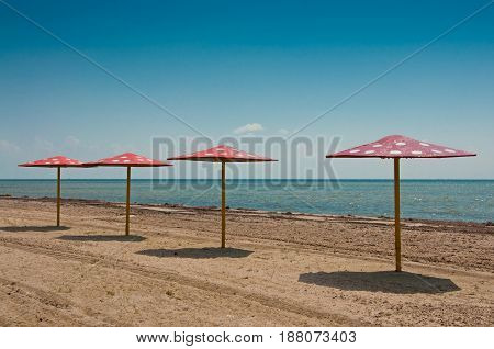 Four parasols on the empty sandy beach near blue sea water