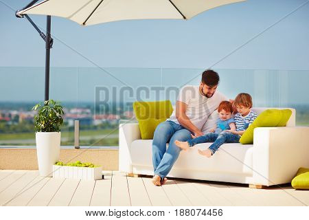 Happy Family Relaxing On Roof Top Terrace At Warm Sunny Day