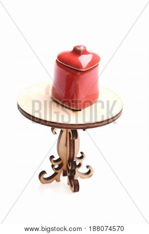 Sugar bowl in red colour and shape of heart with cover on it standing on tiny wooden table isolated on white background close up. Tiny set of kitchenware and vintage concept