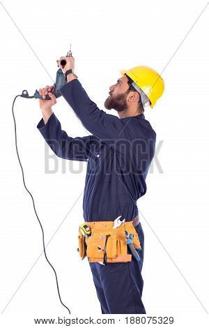 Smiling beard young worker drilling by driller tool and looking up man wearing workswear and belt equipment isolated on white background