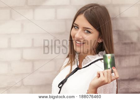 Beautiful Smiling Woman Holding A Card In Hand