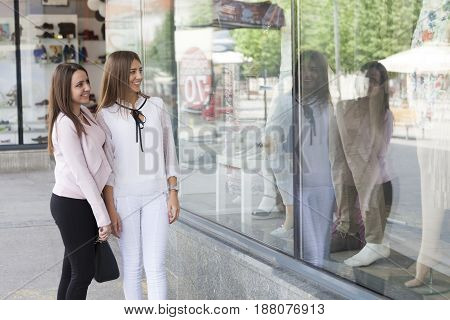Two young beautiful woman looking at the a store window. Positively surprised.