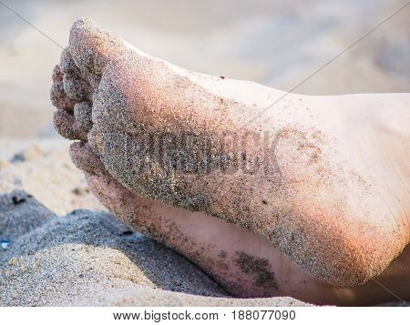 Feet Of One Unrecognizable Caucasian Person Resting In Sand, With Wet Sand On Foot Soles