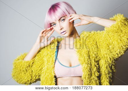 Portrait of beautiful girl with pink hair on white background