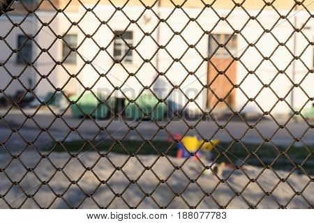 Behind The Fence, Desolate Children's Playground Near A Residential House In The Daytime In City