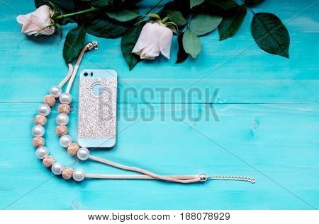 Spring background layout on a blue wooden background with flowers rose and rose petals telephone and beads accessories