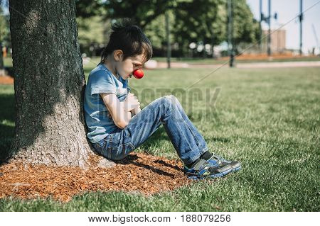 clown boy with red nose is sitting under a tree. kid wearing red clown nose. the concept of Red Nose Day. Copy space for your text