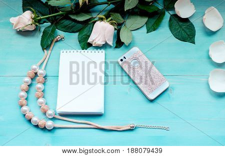 Spring background layout on a blue wooden background with flowers and rose petals Notepad sheets for records of phone and beads accessories