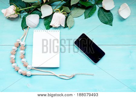 Spring background layout on a blue wooden background with flowers and rose petals Notepad sheets for notes and beads accessories