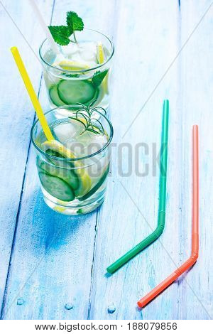 Detox water with lemon and cucumber. Pair of drinking glasses with slices of fresh fruit and vegetable, mint and rosemary. Blue plank background