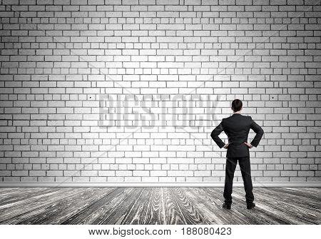 Back view of confident elegant businessman in empty concrete room