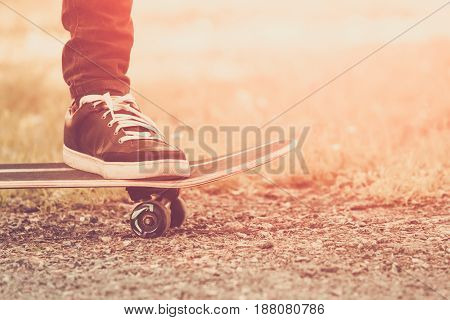 Close up of skateboarders foot while skating in the park
