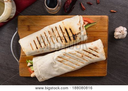 Shaurma chicken roll in a pita with fresh vegetables and cream sauce composition on a wooden background