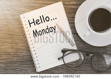 Concept hello monday message on notebook with glasses pencil and coffee cup on wooden table.