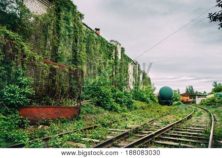 Old industrial railroad station platform, overgrowth with green grass, post apocalypse urbex concept