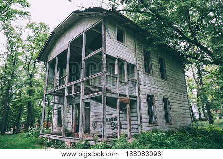Old abandoned rustic wooden mansion house among green trees