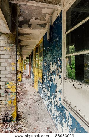Old abandoned children camp building, ruined concrete house, corridor, perspective, vertical image