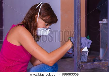Young Woman Paints And Silver Paint Brush
