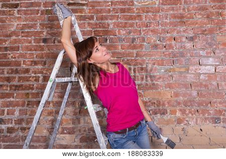 Attractive Woman Painter On Ladder Near Brick Wall