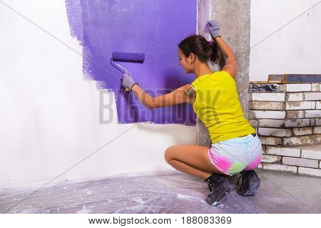 Attractive Woman Paints White Wall Purple Roller