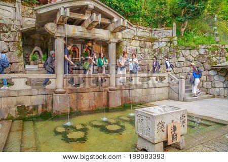 Kyoto, Japan - April 24, 2017: Worshippers drinking water from Otowa-no-taki inside Kiyomizu-dera. The waterfall are divided into three streams and visitors use cups attached to long poles to drink.