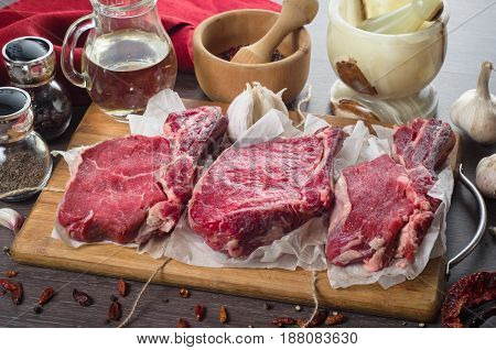 Raw fresh meat rib eye steak composition on a wooden background