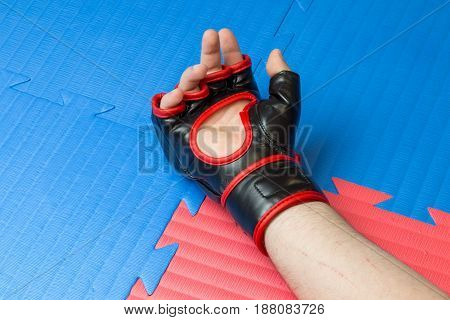 Concept Of Defeat, Loss. Martial Artist Hand Wearing Mix Mma Open Fingers Gloves Touching The Tatami