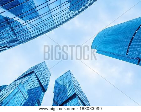 Modern office buildings. Low angle shot of modern glass skyscrapers against the sky Moscow city Russia. Blue toned image