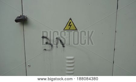 High voltage sign on the door that indicates that beyond that door you can find a place where there is high voltage.