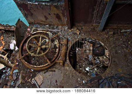 Rusty hatch with the steering wheel Inside rotten abandoned Russian warship