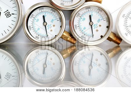 Row of metal steel high pressure gauge meters or manometers with brass fittings on tubing pipeline at LNG or LPG natural gas distribution station plant or factory facility isolated on white background.Pressure gauge in oil and gas production process.