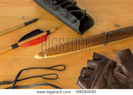Conceptual Image Of Archery. A Wooden Long Bow, Arrow Tip, Arrow Back Feather, Gloves, Arm Guard Pro