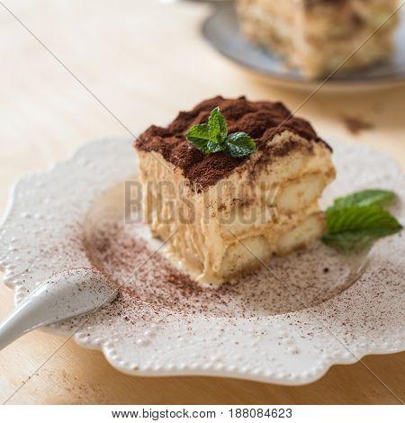 homemade tiramisu cake on white plate, wood background