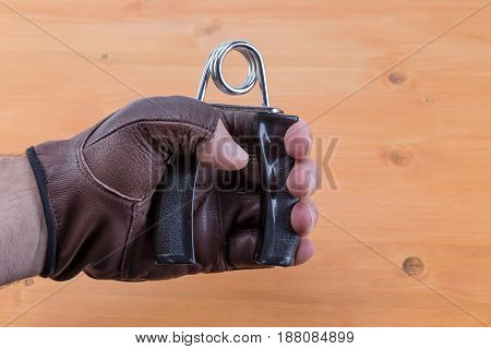 Man Wearing Open Fingers Gloves Using Hand Grips To Exercising Fingers And Staying Fit. Oak Wood Tab
