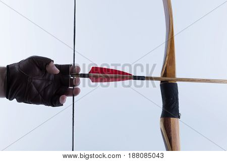 Archer Wearing Open Fingers Leather Gloves Drawing A Traditional English Longbow With A Red Feather