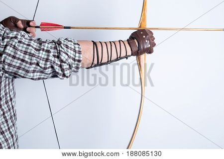 Side View Of An Archer Wearing Open Fingers Leather Gloves, Checked Shirt, And Arm Guard, Drawing A