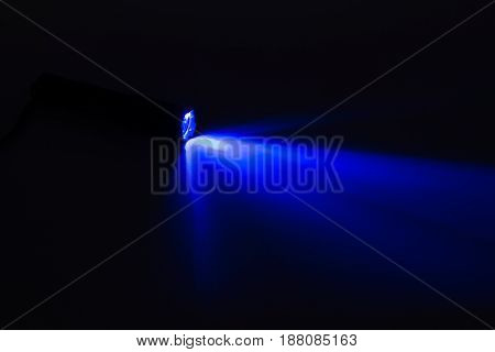 Blue Light Flash Coming From A Flashlight On The Dark