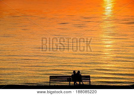 Silhouette of a couple on a bench at sunset against romantic orange colored sea. Summer leisure vacation and romance theme