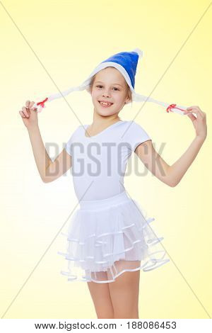 Cheerful little girl gymnast in white sport dress in a cap of Santa Claus.On a yellow gradient background.