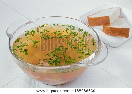 Delicious, Appetizing Light Brown Soup With Herbs In A Transparent Plate. Bread In A White Plate. Ho