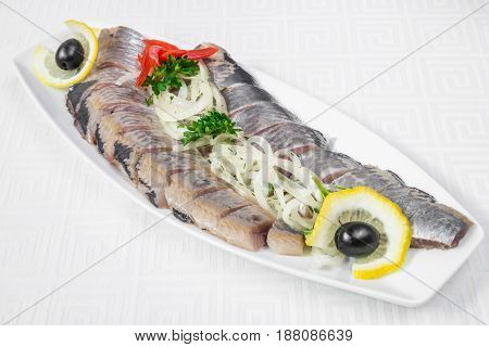 Delicious, Mouth-watering Slices Of Sliced Herring With Onion Rings, Lemon And Herbs, On A White Pla