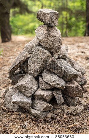 Background wild stones laid out in a pyramid against the background of the forest on the whole frame