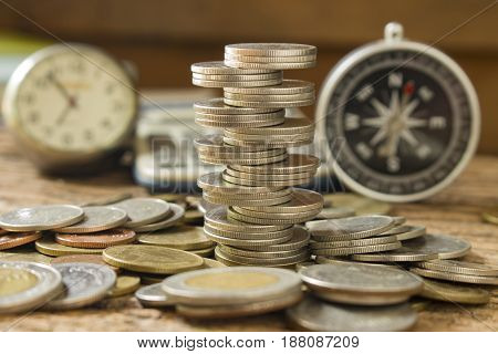 stack of coins with blurred compass and time concept saving money or direction of profit