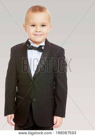 Beautiful little blond boy in a fashionable black suit with a tie.On a gray background.