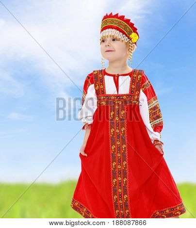 Cute little girl in Russian folk dress. She holds the edge of the dress by hand.On the background of green grass and blue sky with clouds.